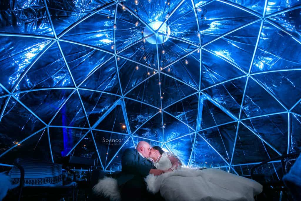 bride and groom kiss in front of twinkle lights at Vosh