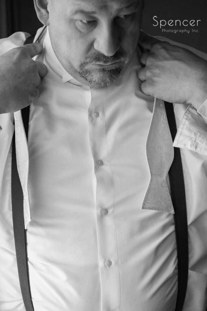 groom tying his bowtie on wedding day in Lakewood
