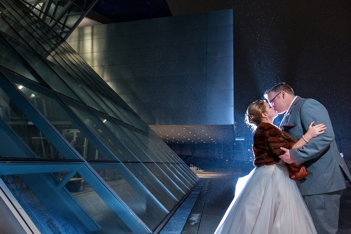 couple kissing in front of Akron Art Museum on wedding day