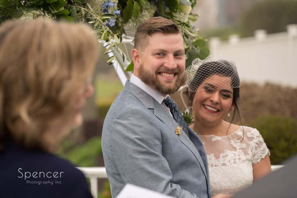bride and groom listen to mom sing at wedding ceremony