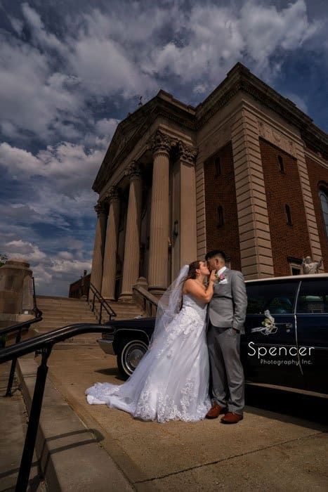 bride kissing groom outside of Mary Queen of Peach Church Cleveland