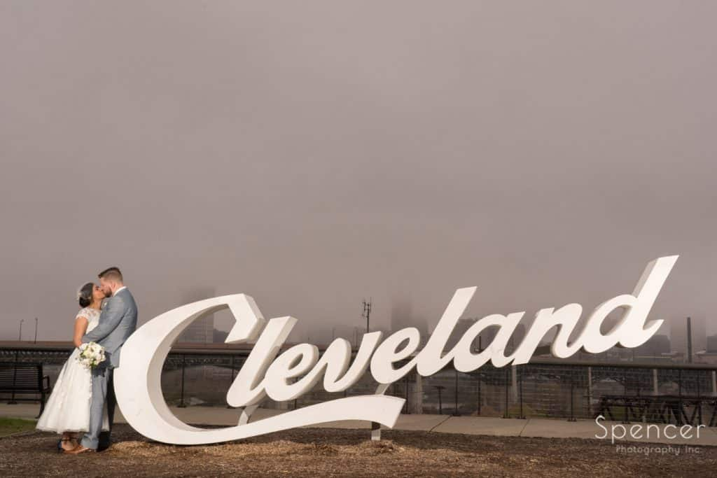 bride and groom kissing by Cleveland sign on their wedding day