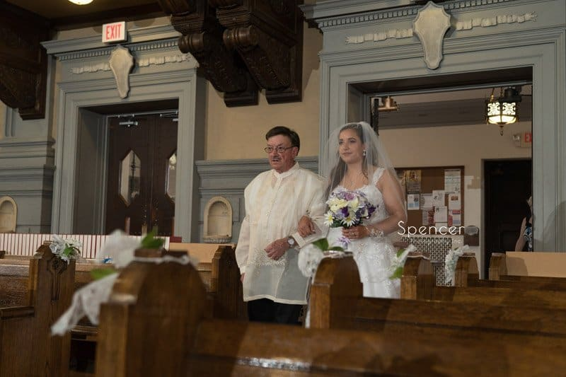 bride walking down aisle at wedding ceremony at Mary Queen of Peace