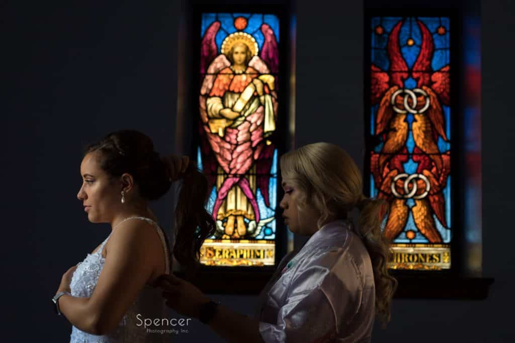 bride putting on wedding dress at Mary Queen of Peace church