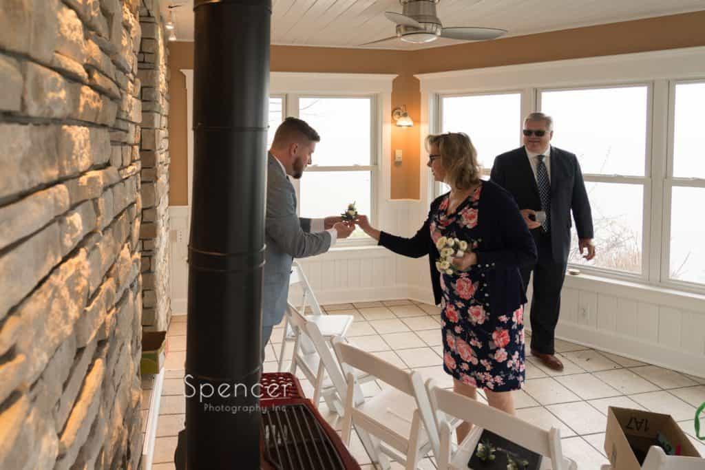 mom at Geneva wedding handing groom flowers