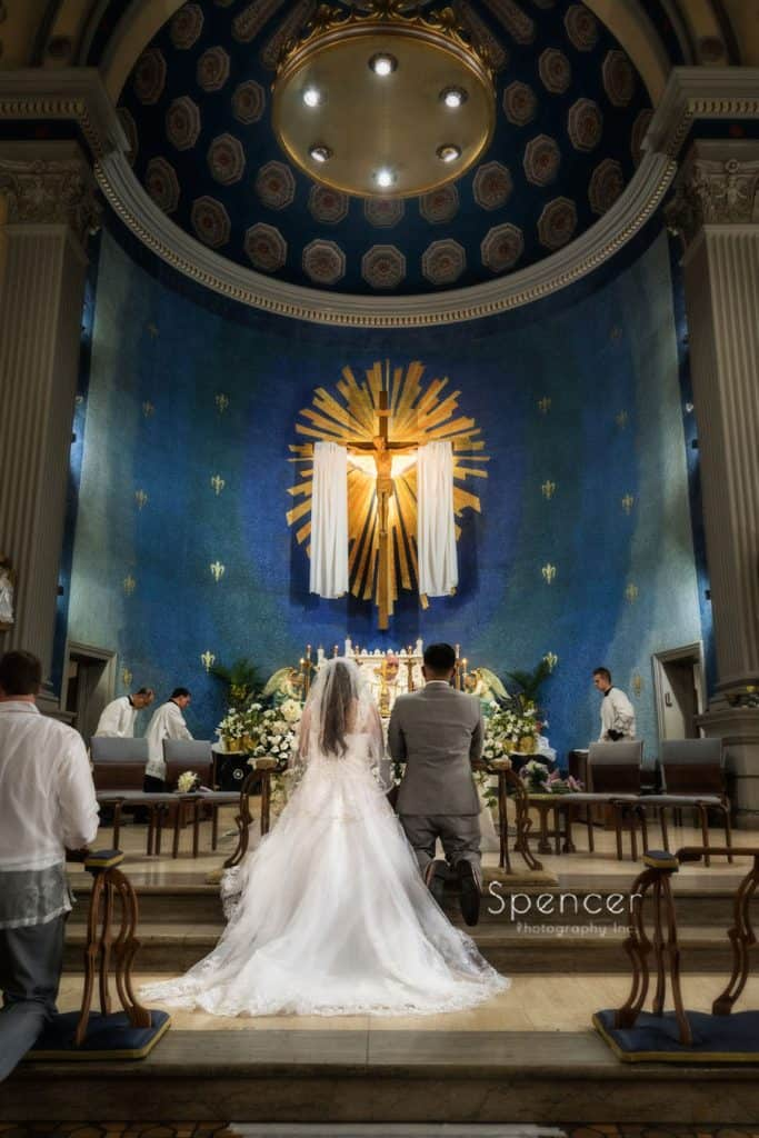 bride and groom kneeling on altar at wedding ceremony at Mary of Peace Chruch