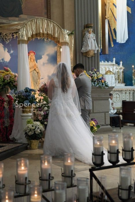 bride and groom honoring Mary at wedding ceremony
