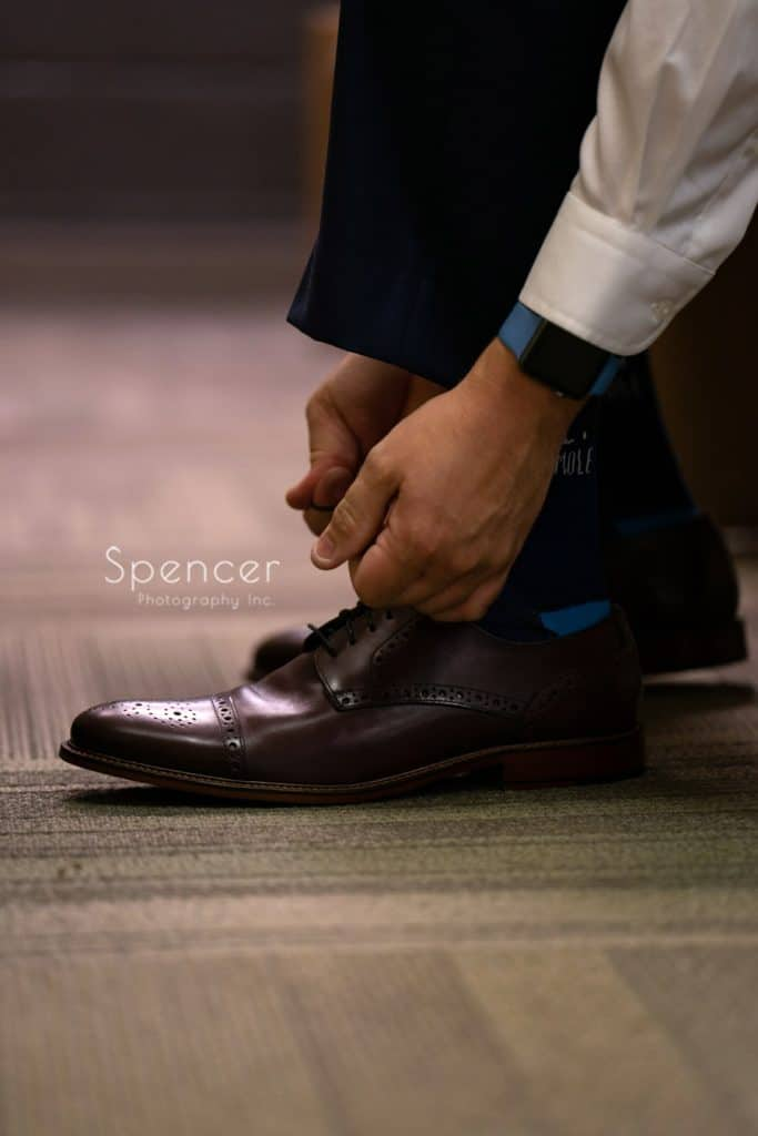 groom tying his wedding day shoes