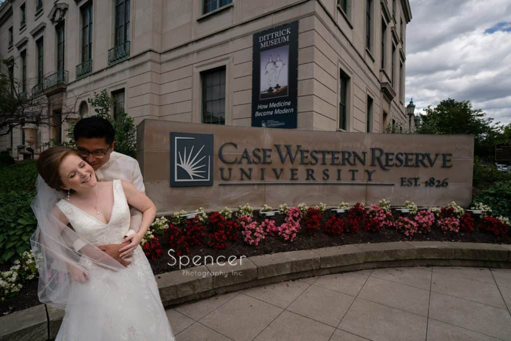 bride and groom laughing in front of Case Western Reserve sign in Cleveland