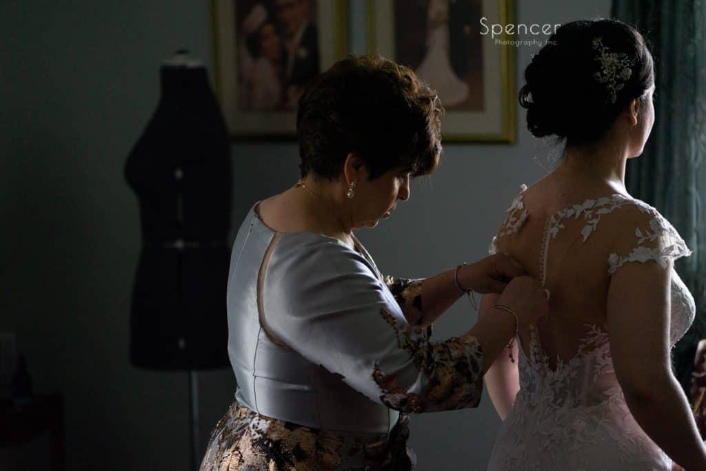 brides mom buttoning her wedding dress