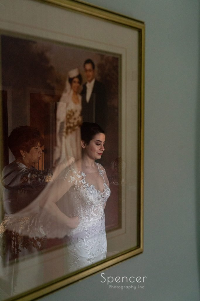 reflection of mom helping bride into her wedding dress
