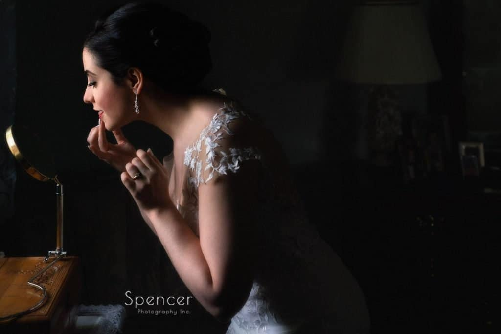 bride adjusting lipstick on wedding day in Youngstown