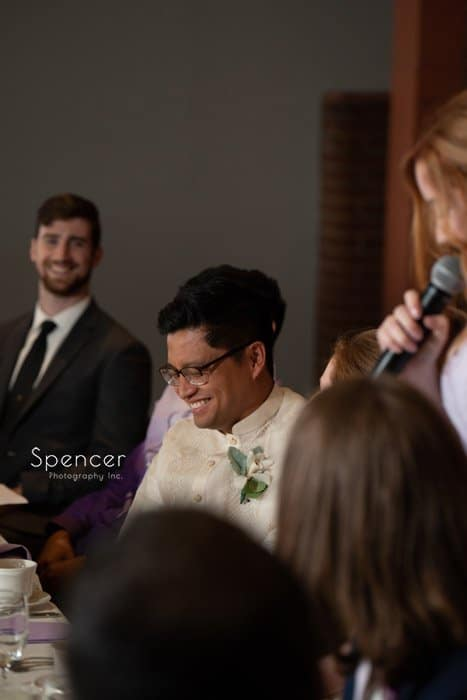 groom laughing at maid of honor speech