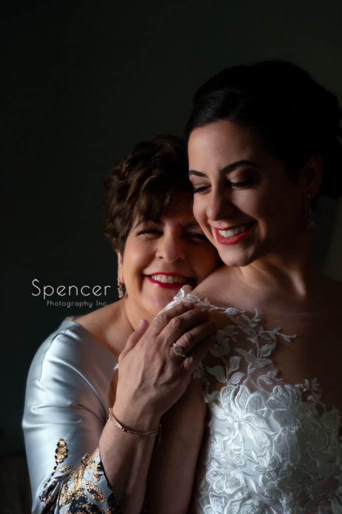 mom hugging bride on wedding day