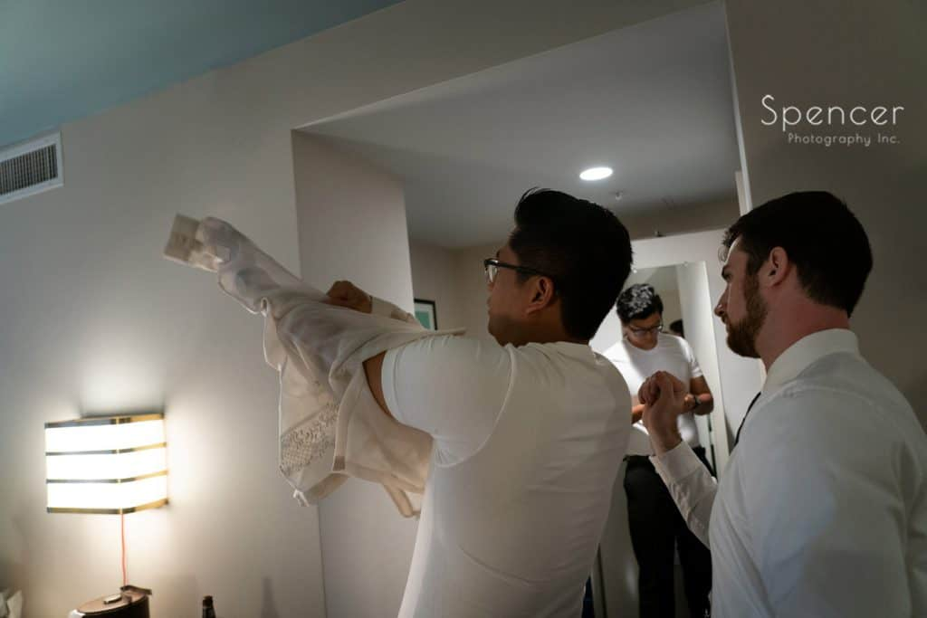 groom putting on his fillipino wedding shirt