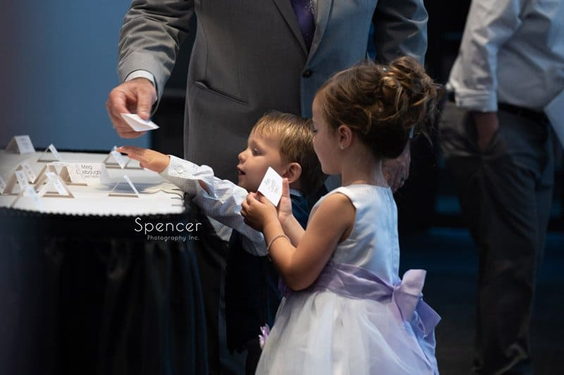 ring bearer grabbing name card at Windows on the River