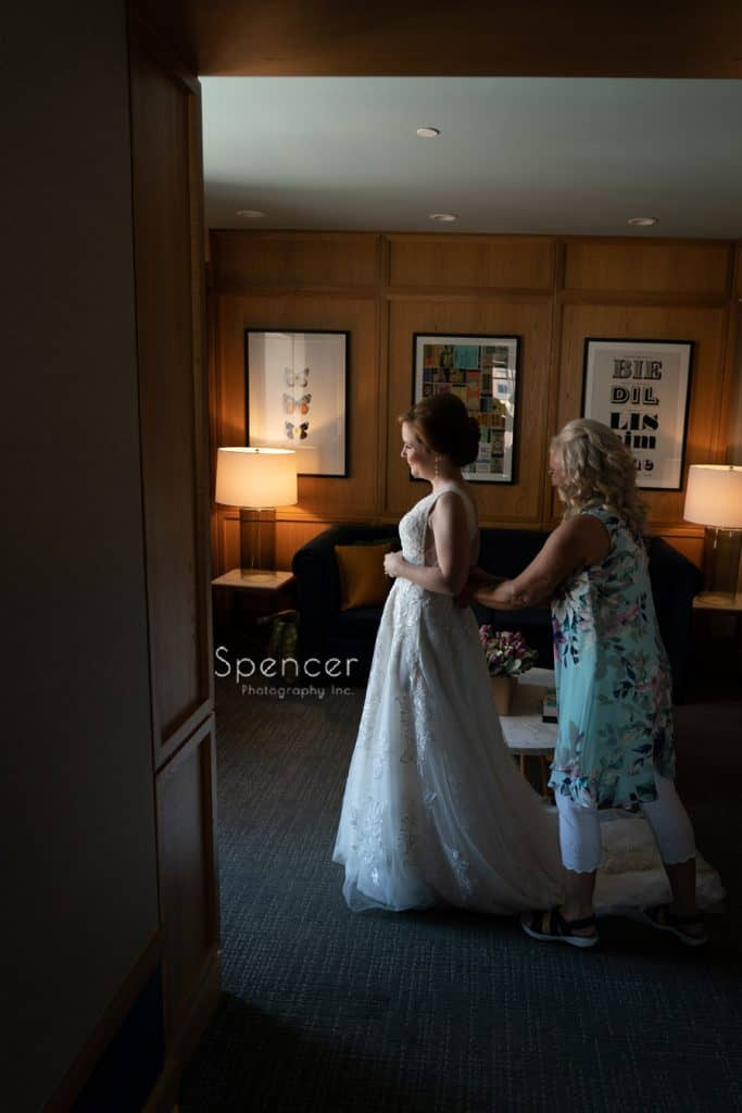 bride putting on wedding dress at Kimpton Schofield Hotel