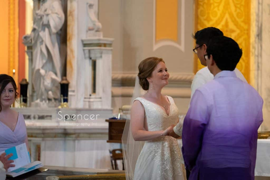 bride smiling at groom on altar of St. Coleman Cleveland
