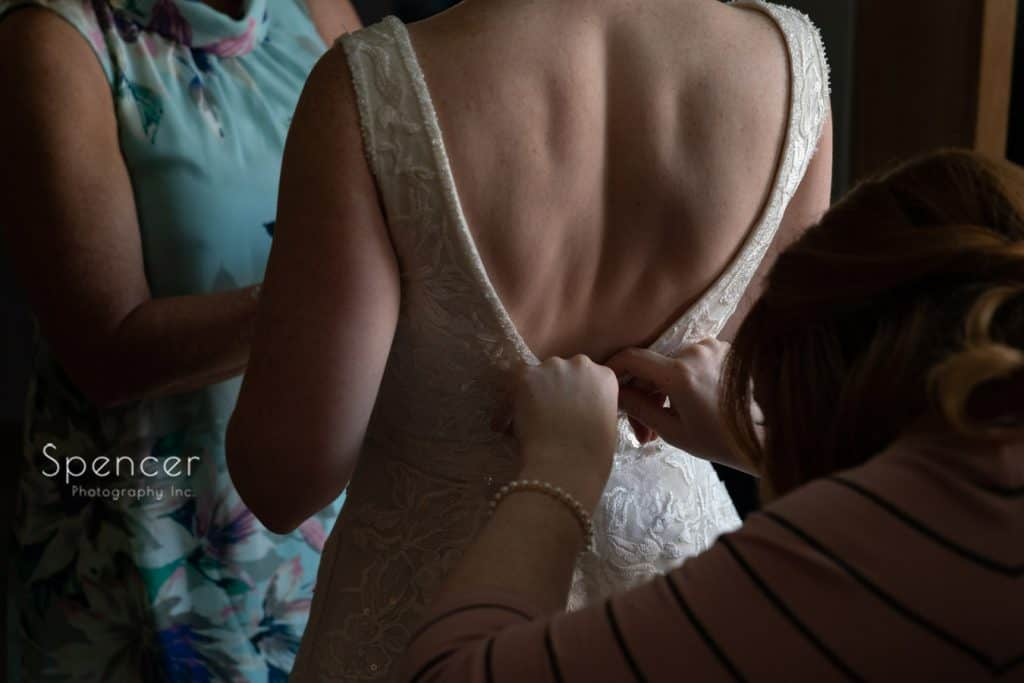 bridemaid helping bride into wedding dress