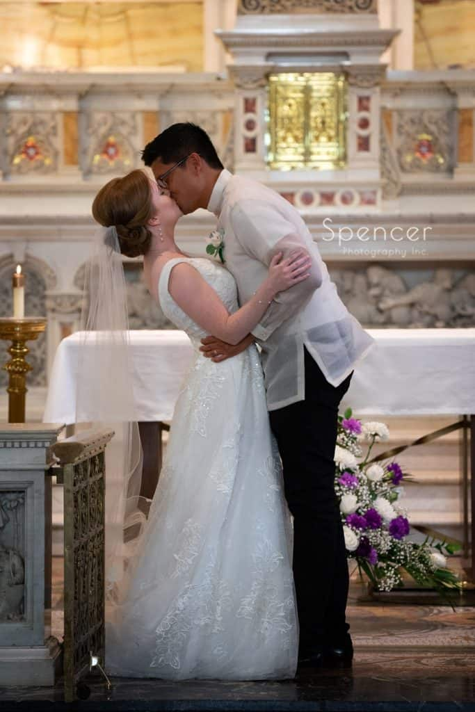 first kiss at wedding ceremony at St. Coleman Church