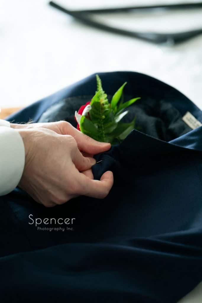 groom pinning on wedding day boutonniére at Avalon Hotel Youngstown