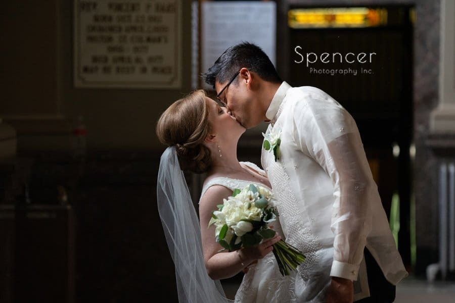 groom kisses bride after wedding ceremony at St. Coleman Chruch Cleveland