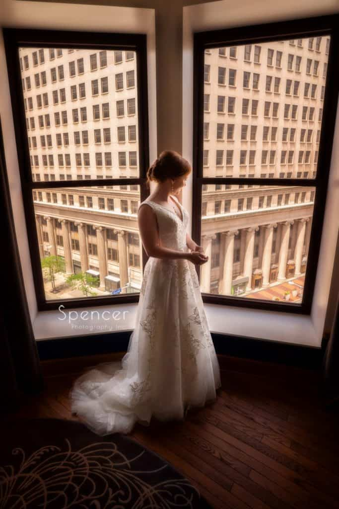 bride standing in her wedding dress at window at Kimpton Schofield Hotel Cleveland