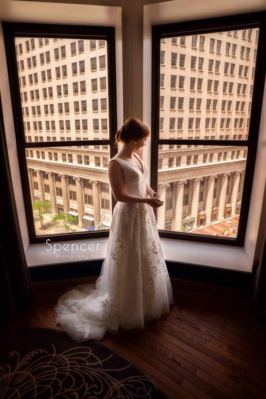 bride standing in her wedding dress at window at Kimpton Schofield Hotel Cleveland