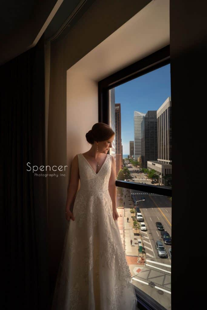 bride looking out window at Kimpton Schofield Hotel in Cleveland