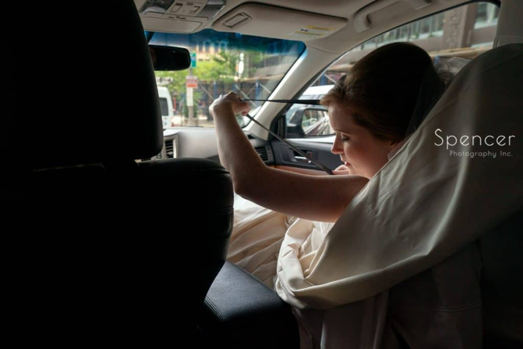 bride putting on her seatbelt to leave for her Cleveland wedding