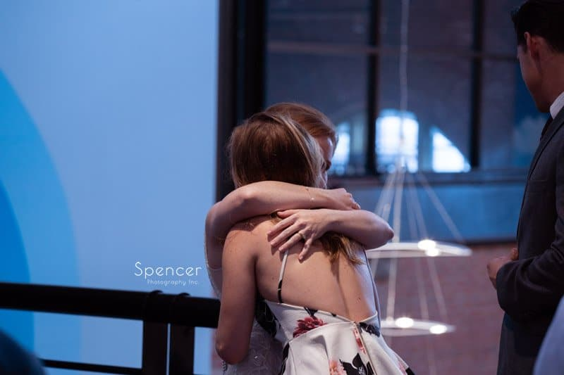 bride hugging guest at wedding reception at Windows on the River