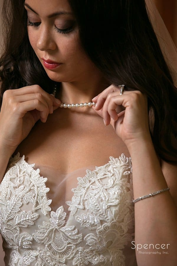 detail picture of bride holding her wedding day necklace