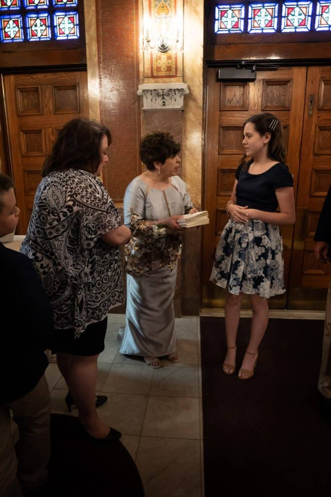 mother of bride pass out wedding programs at St. Demetrios