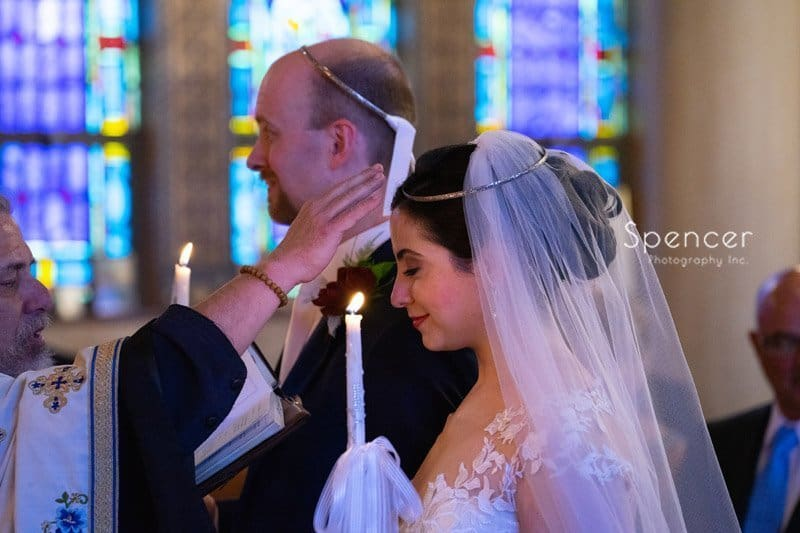 priest blessing bride at wedding ceremony