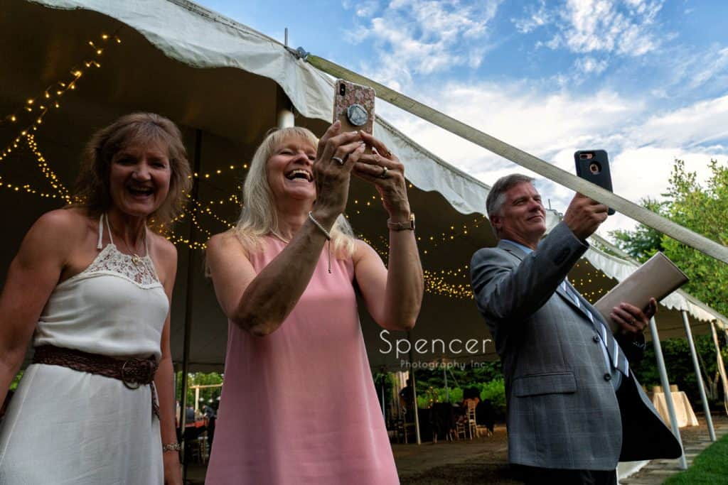 guest photographing bride and groom entering wedding reception