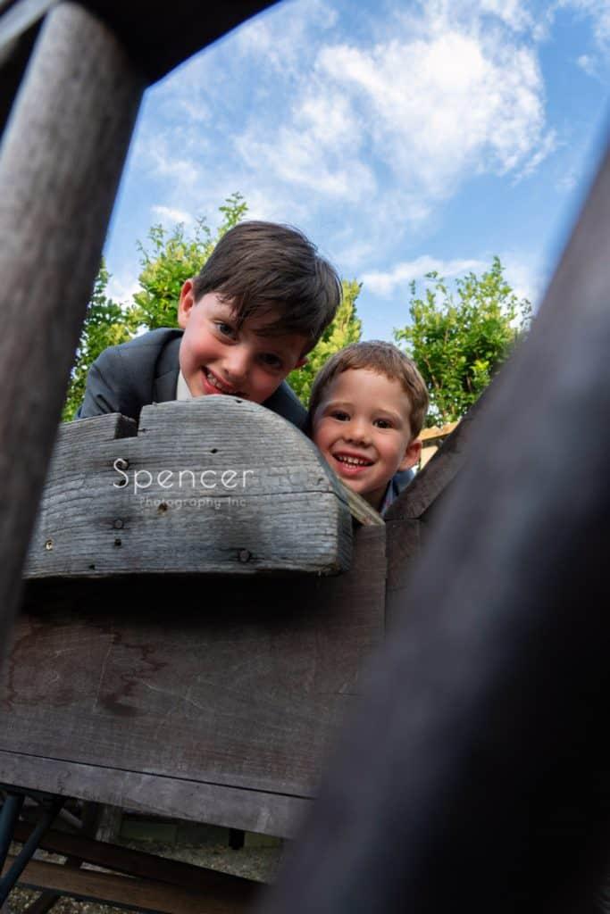 kids smiling into camara thru wagon wheel at Thorncreek