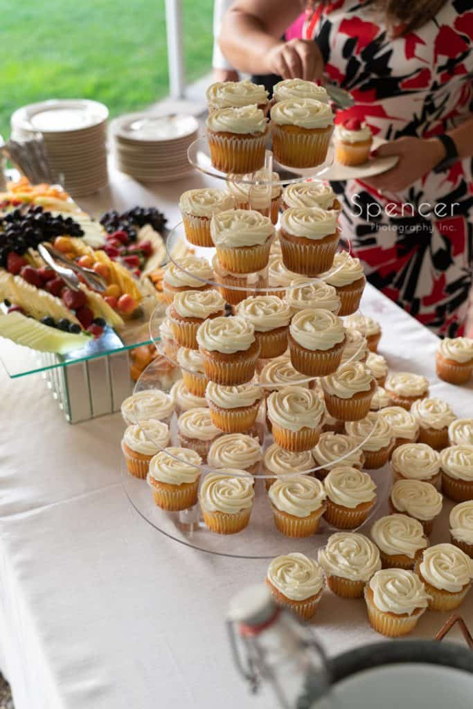 cupcake table at tented wedding reception