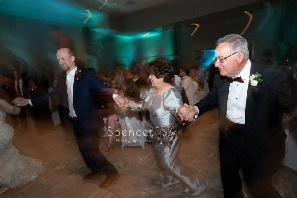 groom dancing with brides parents at St. Demetrios