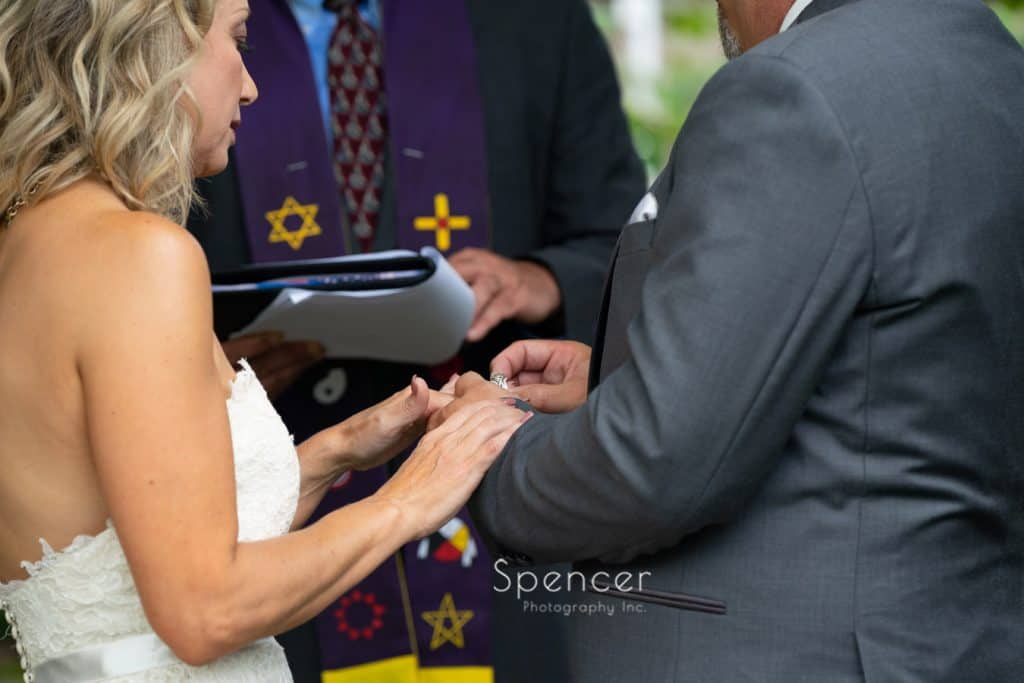 groom putting on wedding ring during ceremony at Thorncreek
