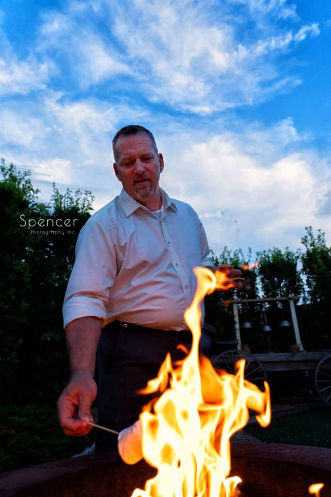 groom at his Thorncreek reception cooking s'mores