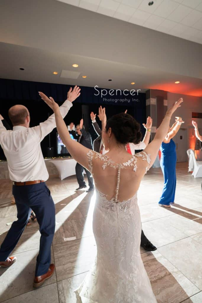 bride waving arms and dancing at her wedding reception