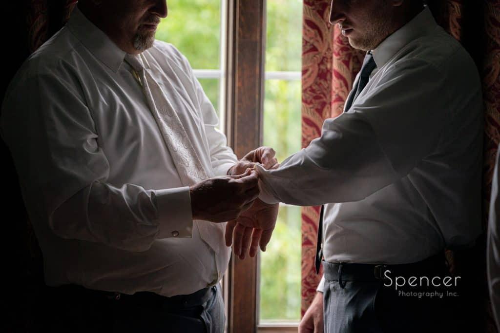 dad helping groomsman prep for wedding at The Bertram