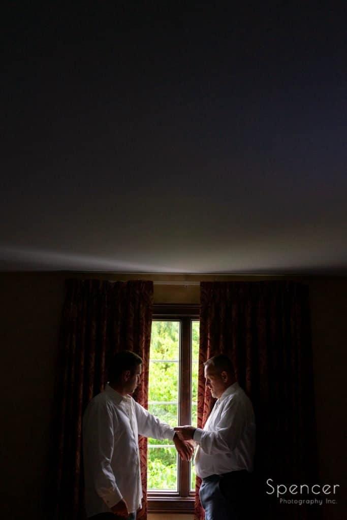 groom helping groomsme get ready for wedding at The Bertram Inn