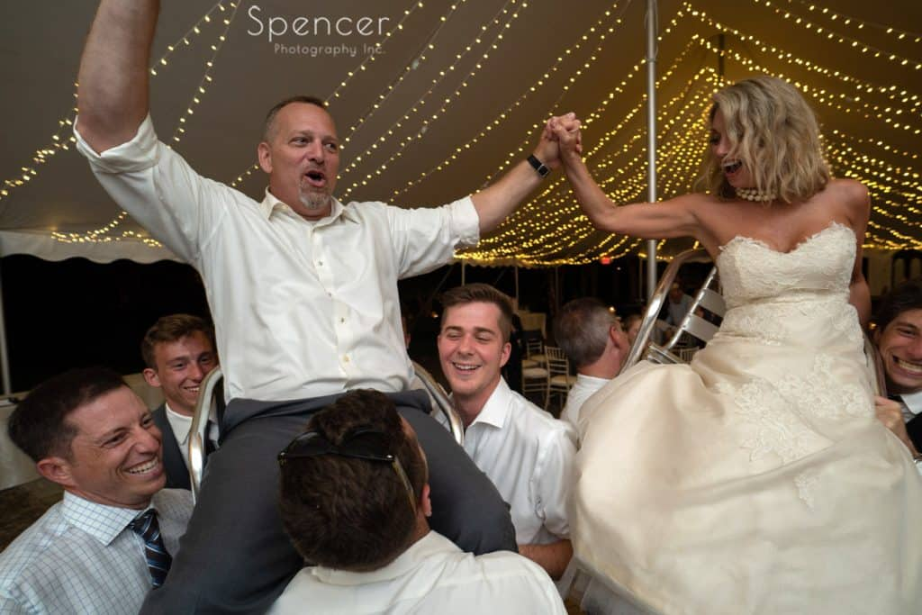 bride and groom being lifted onto chairs during reception