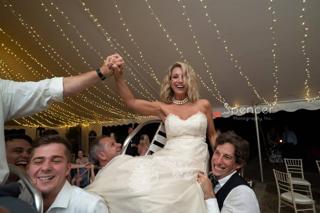 bride laughing while being lifted in chair