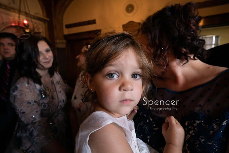 little girl being held by mother at wedding ceremony