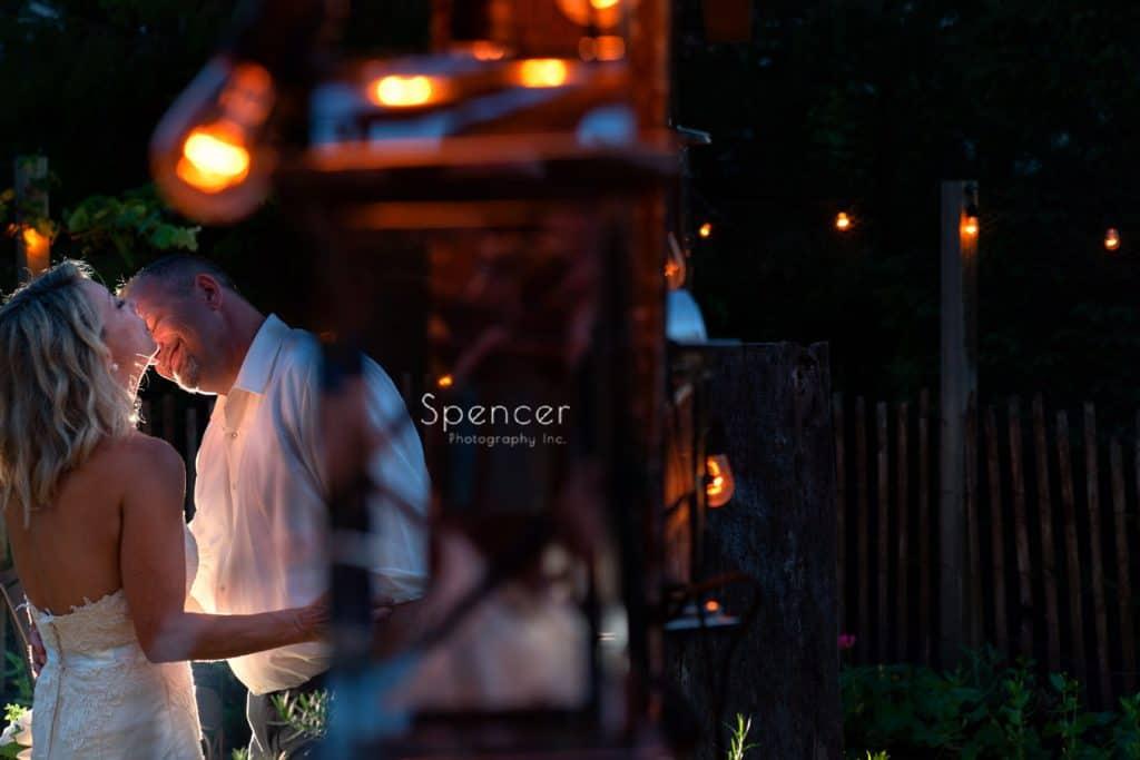 groom smiling as he kisses bride in gardens of Thorncreek
