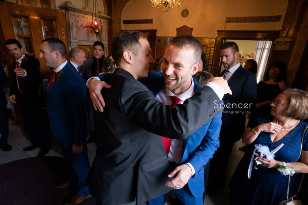 guys laughing and hugging after wedding