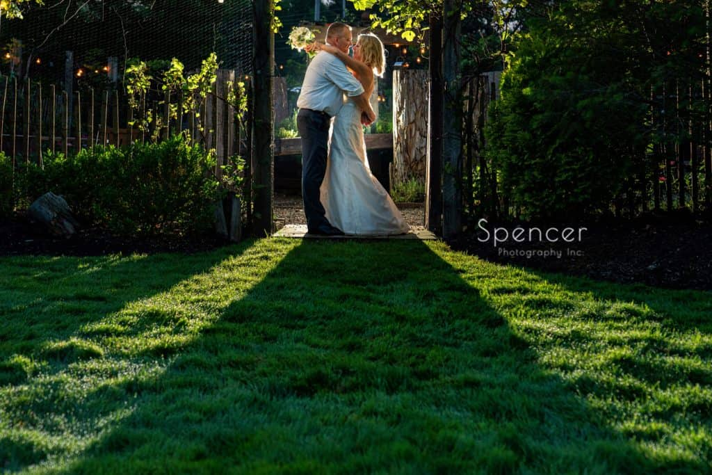 bride holding red twig bouquet while hugging groom at Thorncreek