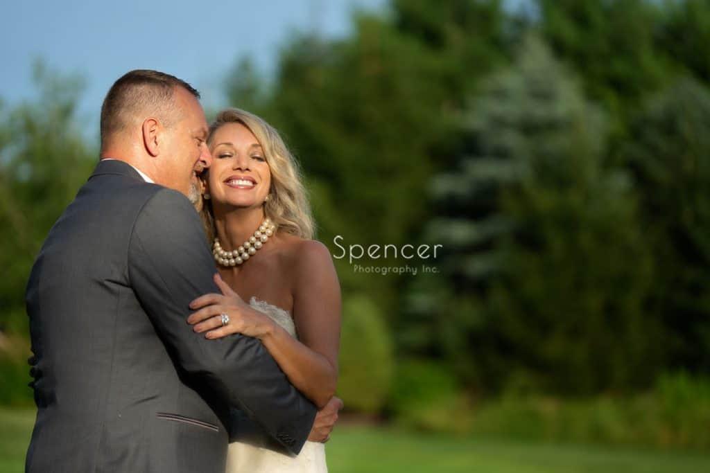 sunlit wedding picture of groom kissing bride